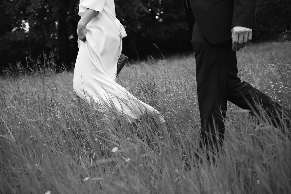 Bride and groom walking in the grass