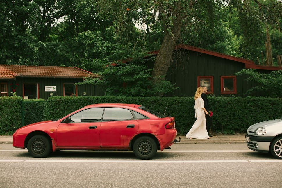 Bride and groom walking in the streets with a red car