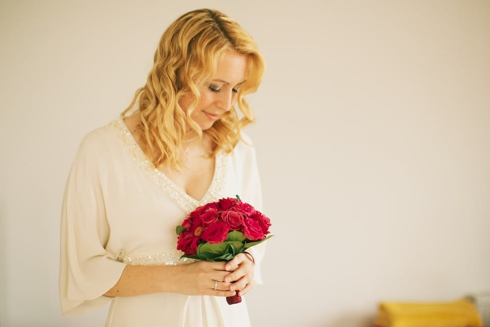 Bride looking at her red bouquet
