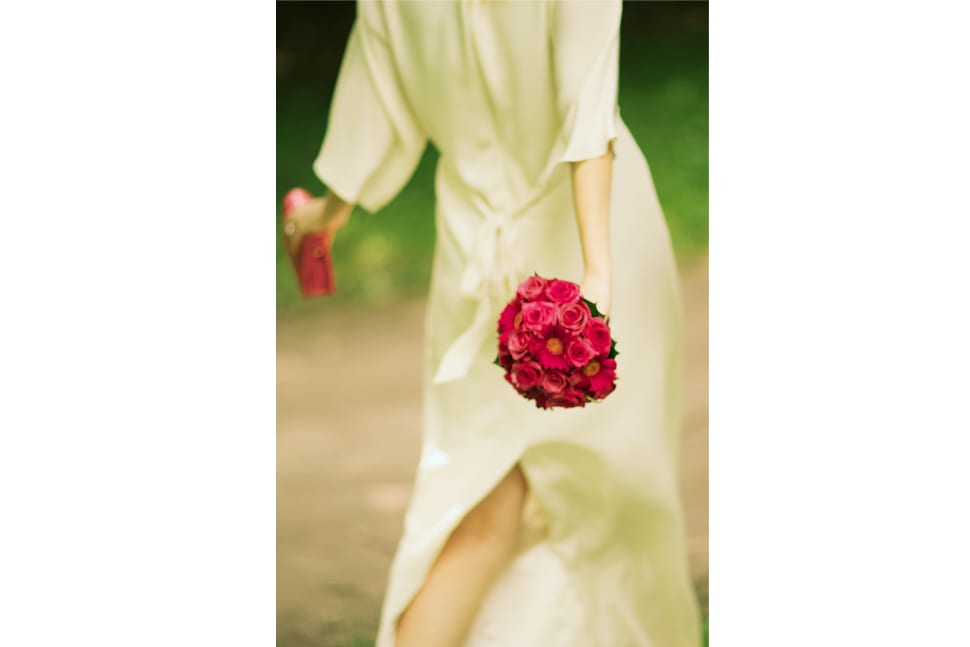 Bride walking with her red bouquet